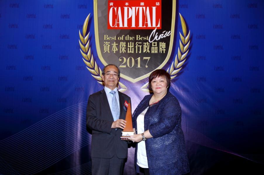 [資本傑出智能電視品牌]: Panasonic,由香港優質顧客服務協會副主席何蕭素嫻女士(右),頒發獎項予信興電器貿易有限公司市務統籌處總經理莫惠明先生(左)。