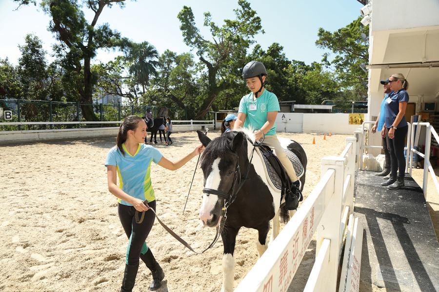 學員在義工及教練的協助下進行復康策騎課程。