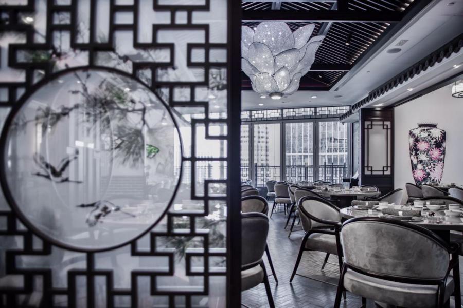主用餐區天花上掛著一盞巨型蓮花形水晶吊燈,非常矚目,與牆上的中式壁畫遙遙呼應著。